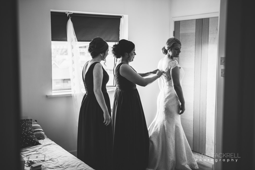 bridesmaids helping bride into dress