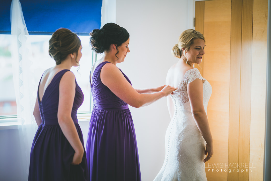 bridesmaids helping bride into her dress