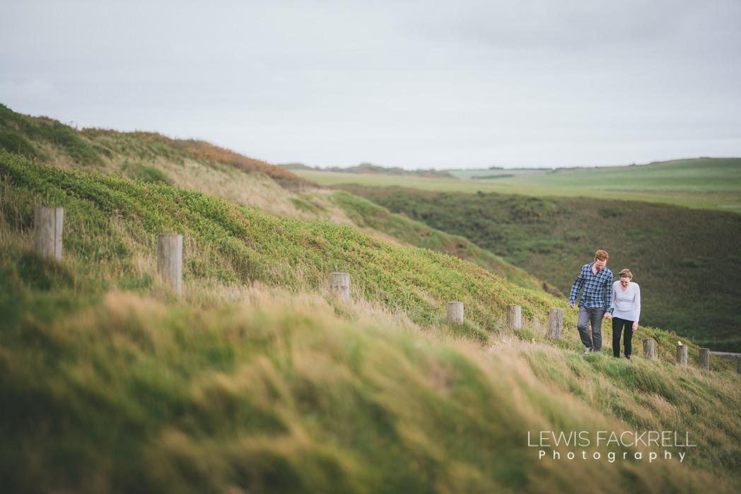 pre-wedding photo shoot couple walking along cliff edge