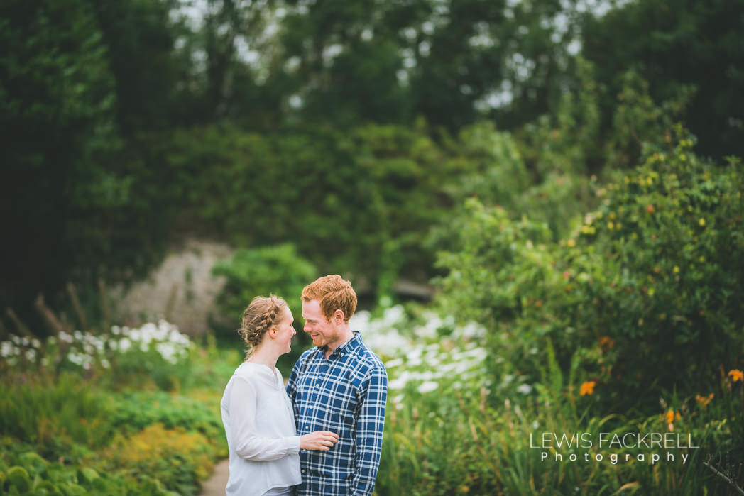 pre-wedding photoshoot Ogmore wedding couple hold and kiss in front of daisies
