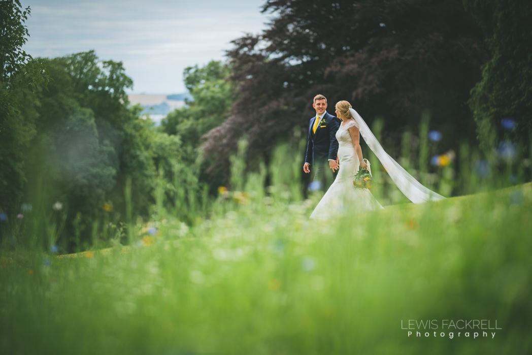 bride groom walk amongst wild flowers