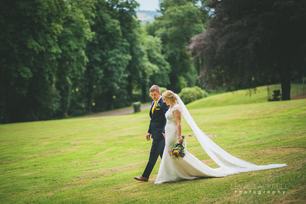Bride groom walk along lawn venue