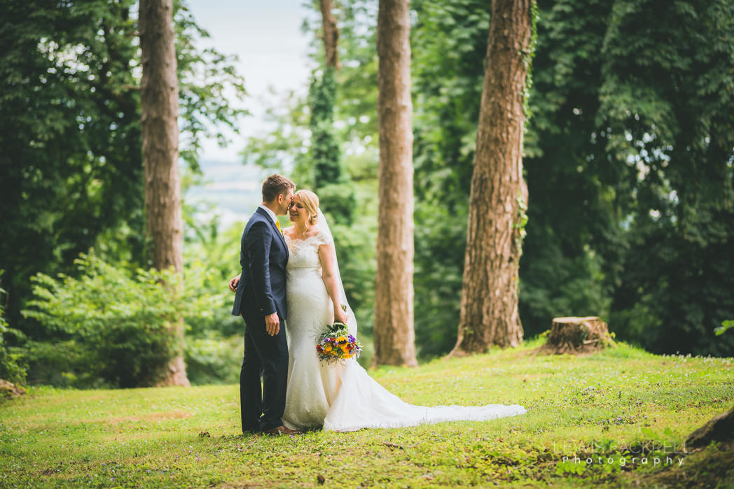 bride and groom holding each other in woodland