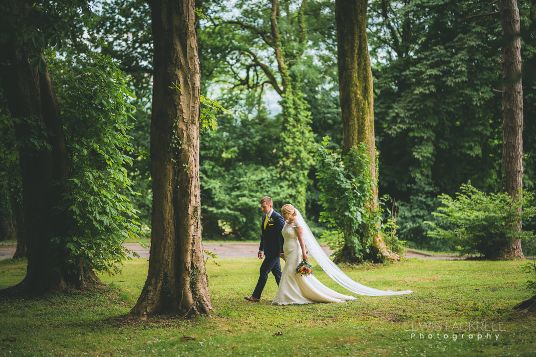 bride and groom walking together through forest