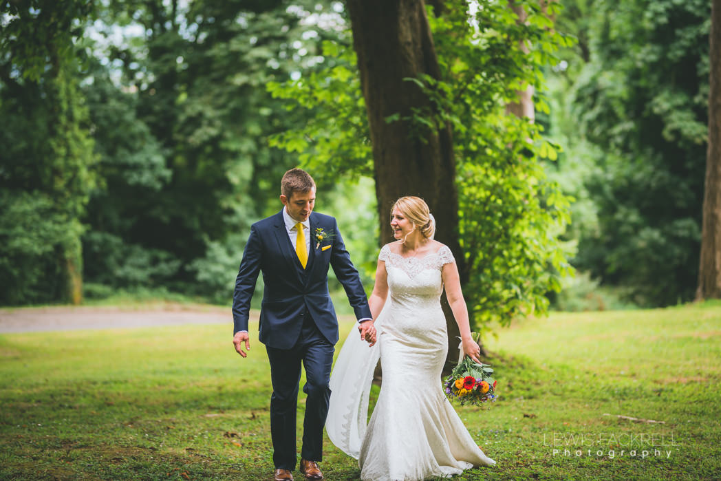 bride and groom walking through woodland