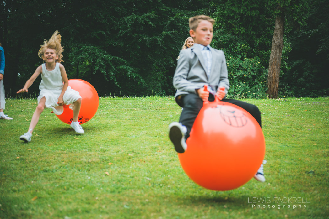 boy on space hopper playing at wedding