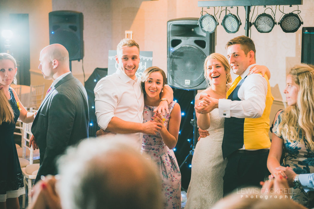 Bride, groom and brother enjoying dancing