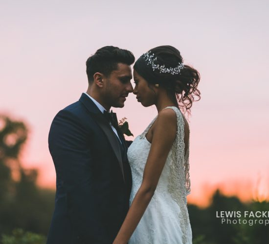 wedding cost and wedding day guide features bride and groom kissing with the backlit sunset