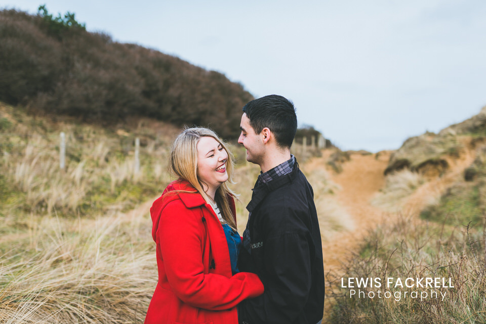 engagement photos in sand dunes with couple laughing ahead of their wedding photography