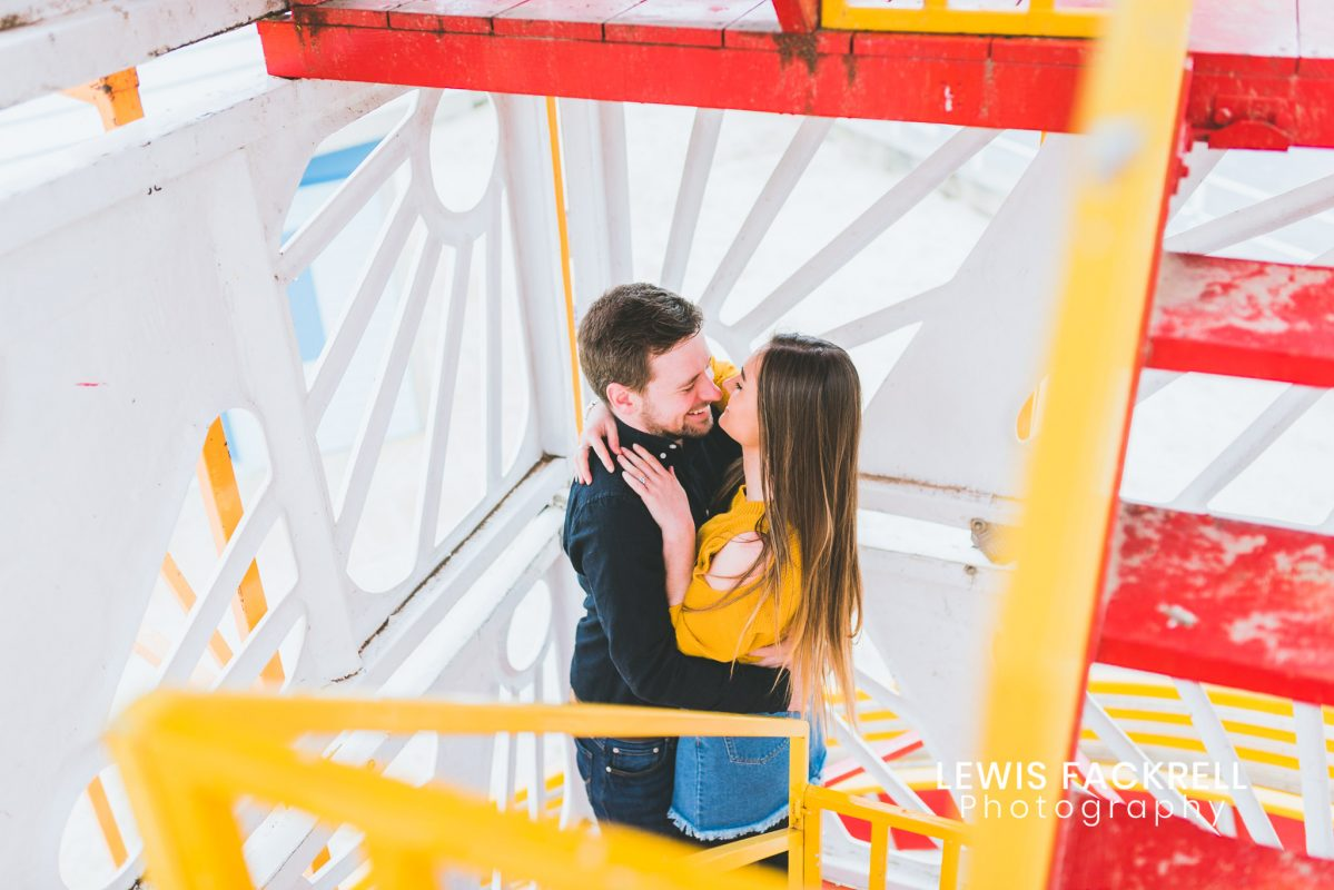 Weymouth pre-wedding photography session of couple on helter skelter