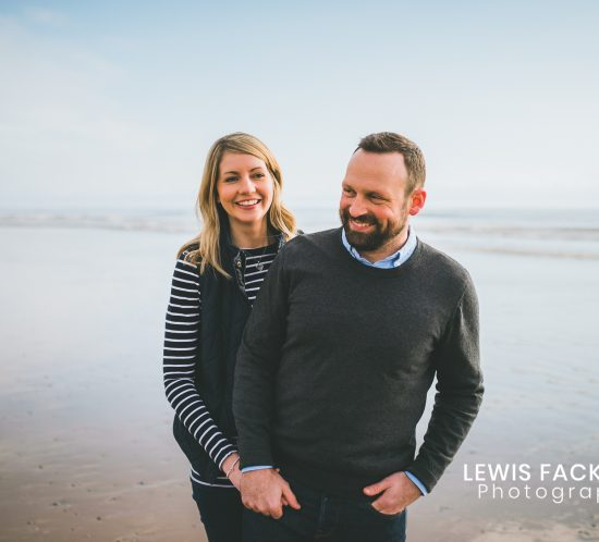 Ogmore pre-wedding photo session of couple cuddling on beach