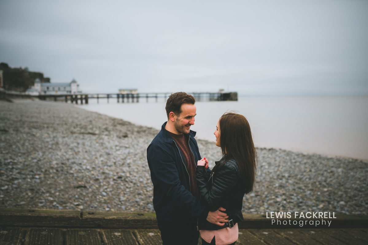 penarth pre-wedding photography couple cuddling with pier in the background