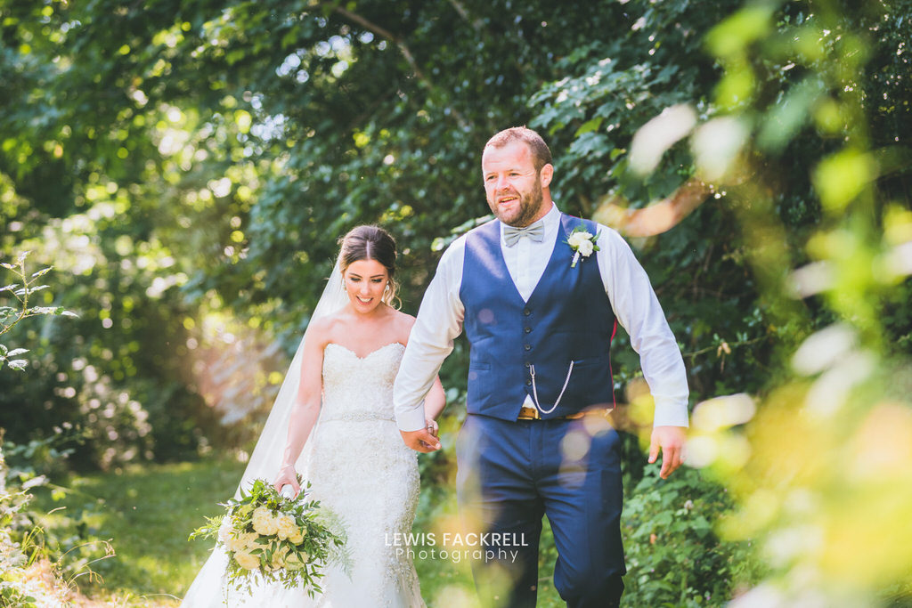 New House Hotel wedding photography of bride and groom walking through field