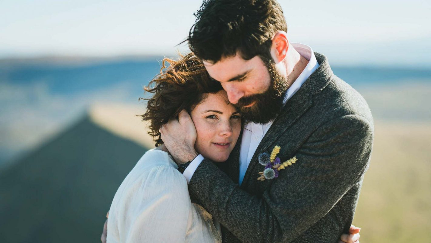 Cardiff Wedding photographers in South Wales with Bride and groom holding each other on top of a mountain