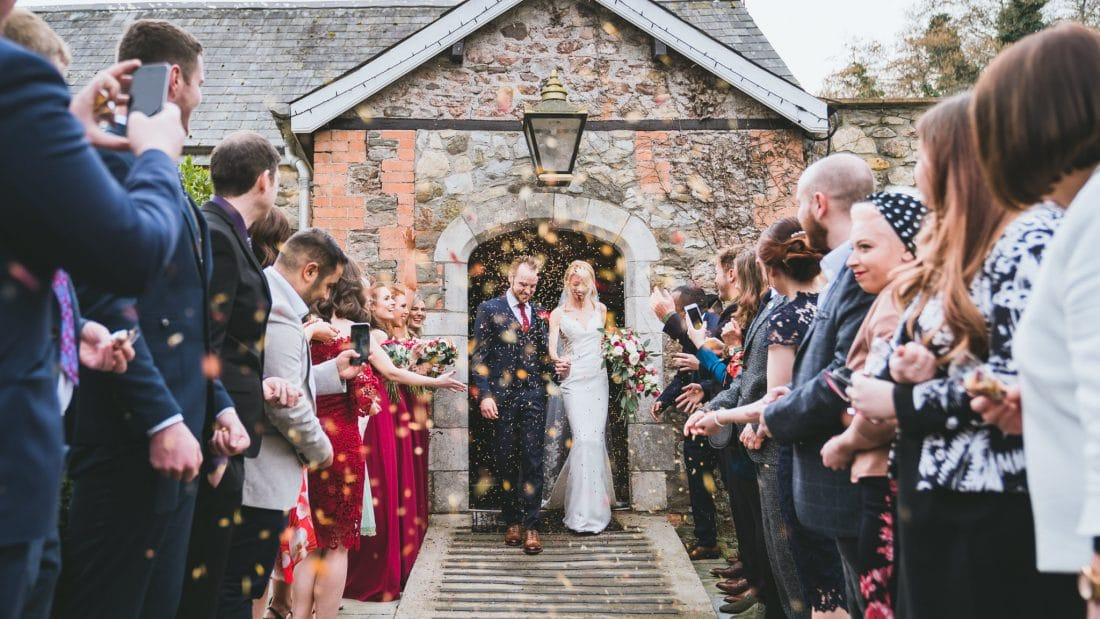 Bride-groom-walking-out-of-pencoed-house-to-guests-and-confetti