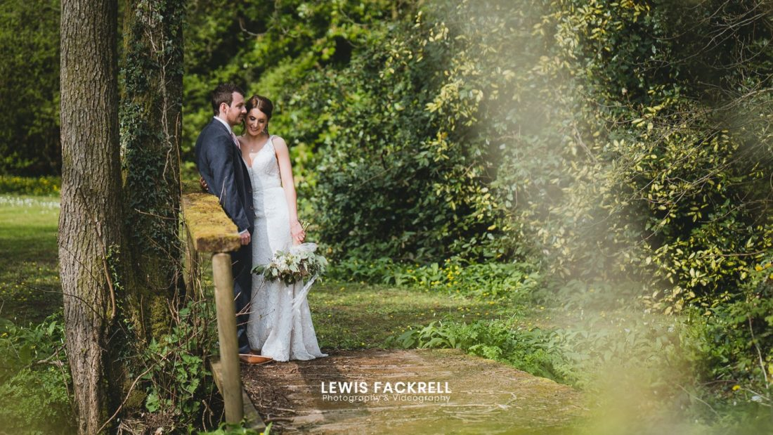 Bride and groom holding each other on the bridge at their wedding at Pencoed House wedding photographers