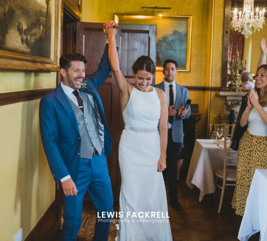 Huntsham Court wedding photography of the bride and groom cheering as they walk into the room for their reception to begin