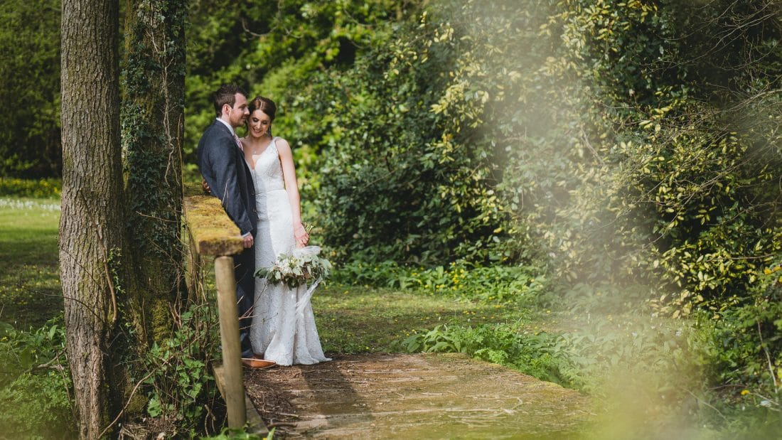 Pencoed house wedding photographers Capturing bride and groom holding each other on the bridge in the garden
