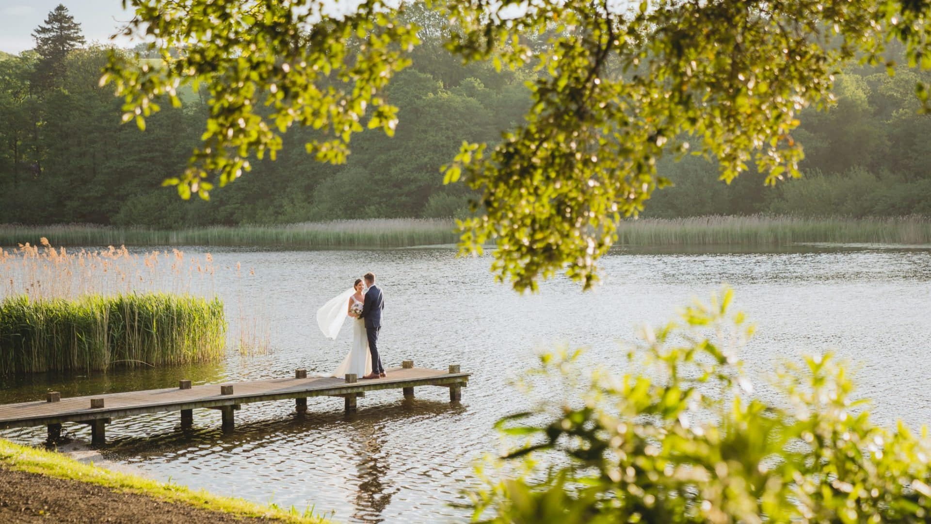 Bride and groom standing on the jetty at their Hensol Castle wedding photography