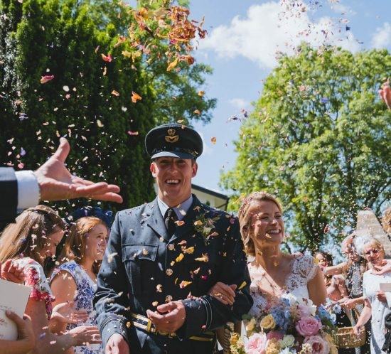 Cardiff wedding photographers in South Wales of lara and kieran coming out of church to lots of confetti