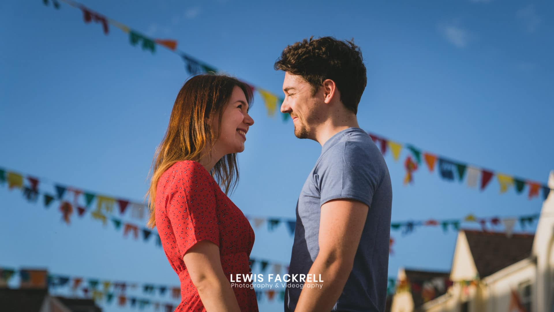 Saundersfoot pre-wedding photography with couple holding each other under the bunting on the high street