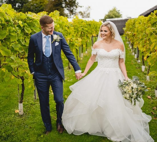 bride groom walking in llanerch vineyard during their wedding photography