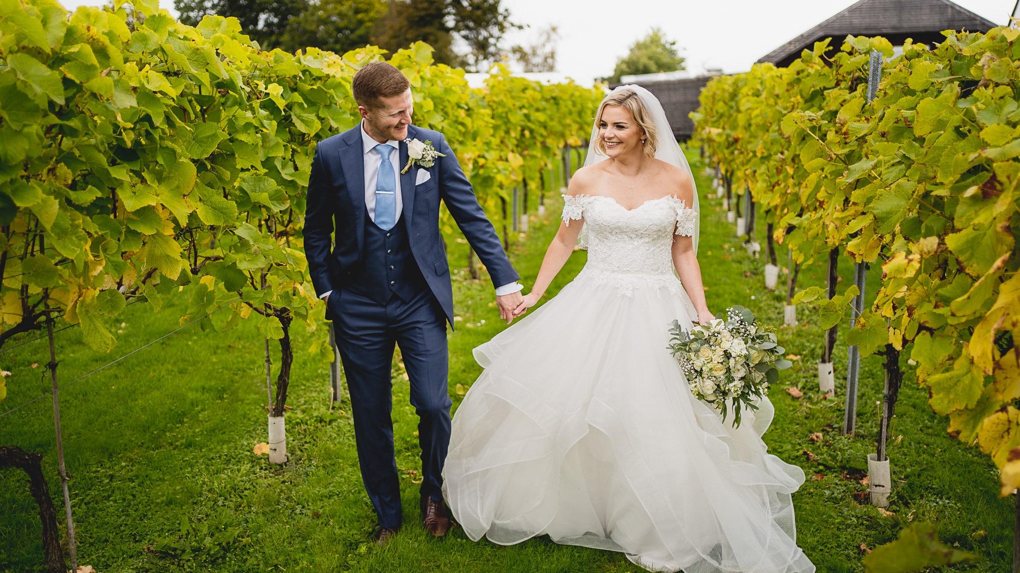 bride groom walking in llanerch vineyard during their wedding photography