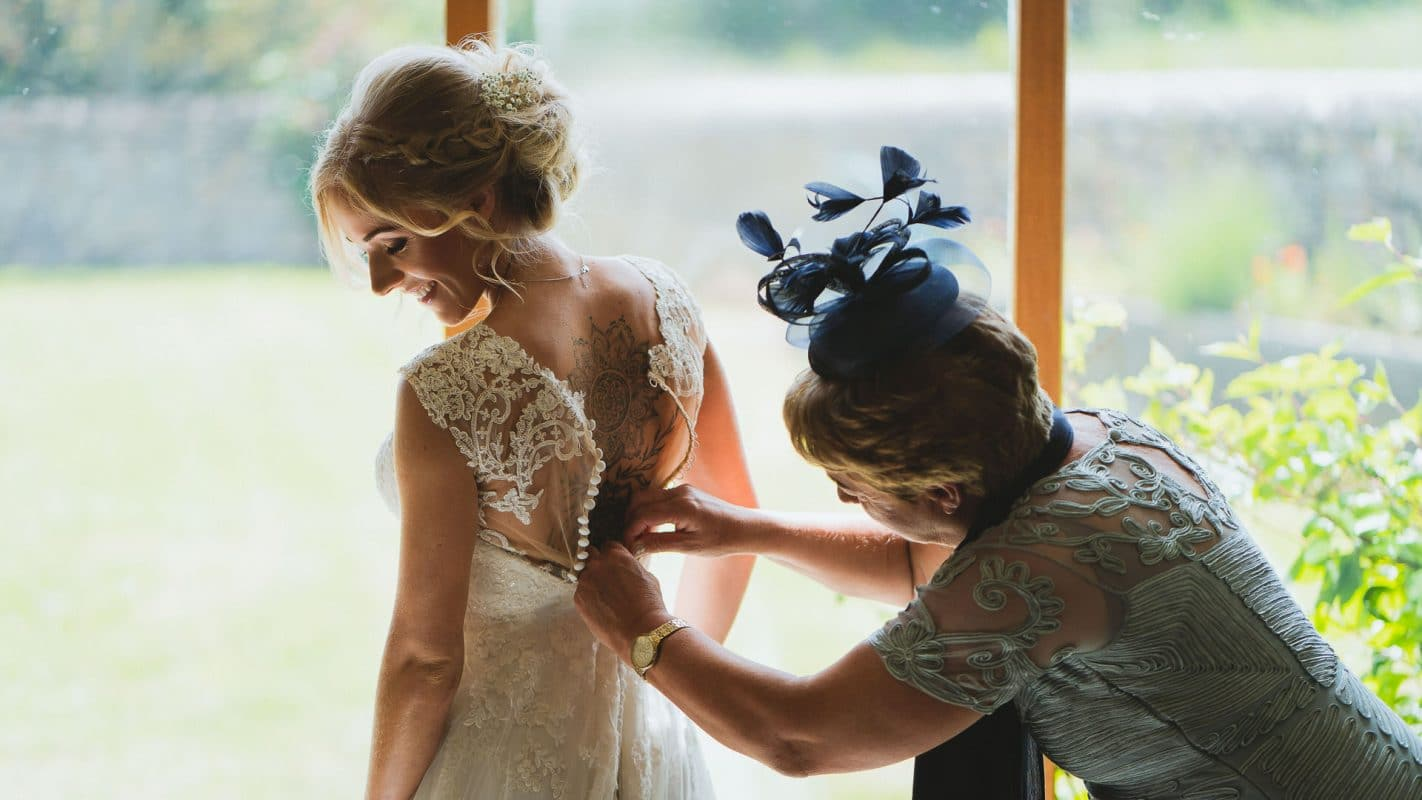 brides mother helping with the dress