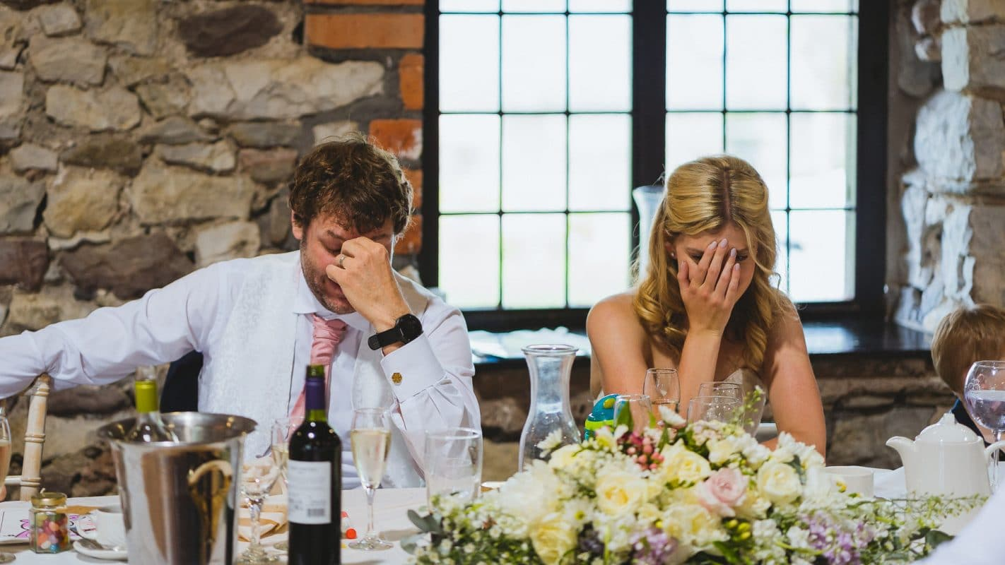 bride and groom facepalming after embarrassing story