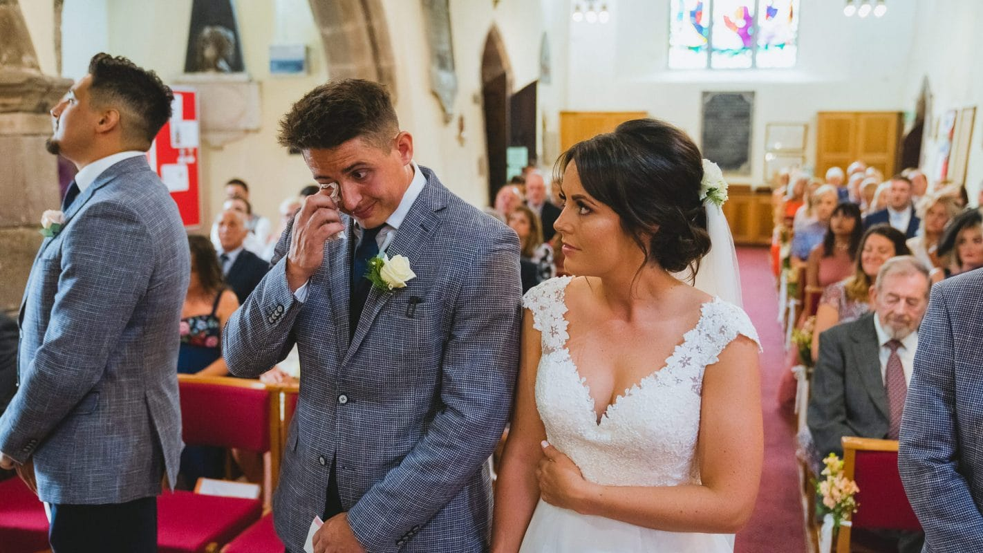 groom crying during reading at wedding