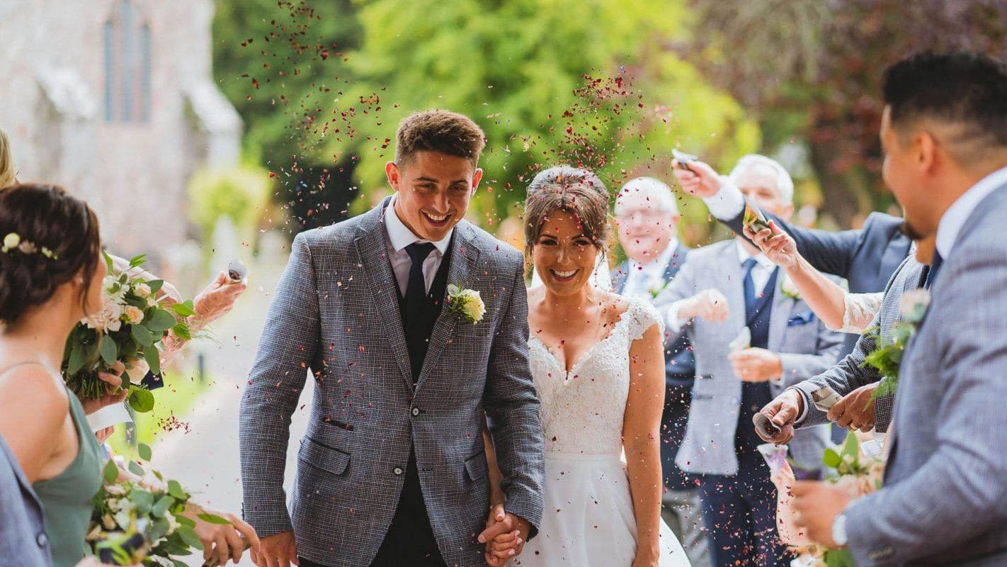 bride and groom walking from church under confetti