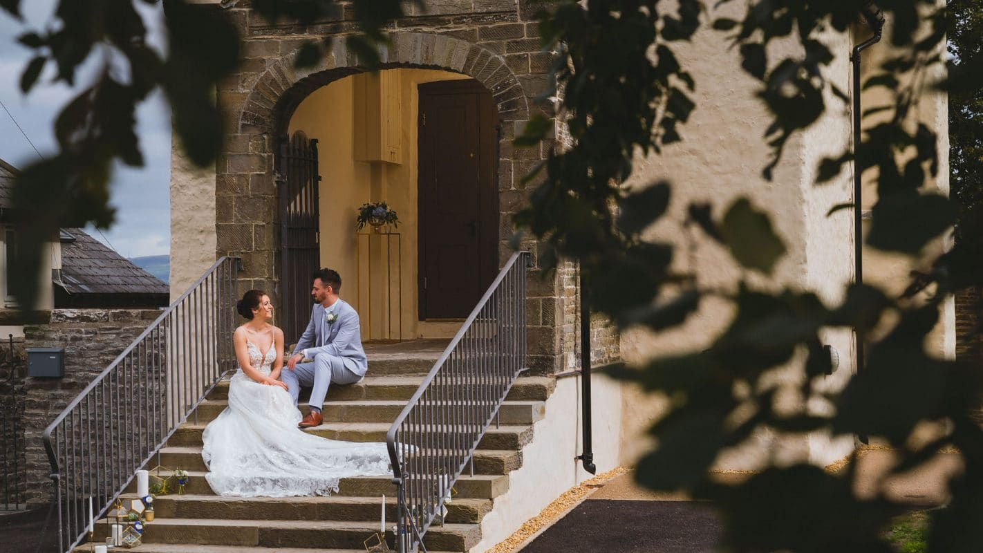 bride and groom sit on the steps after their wedding