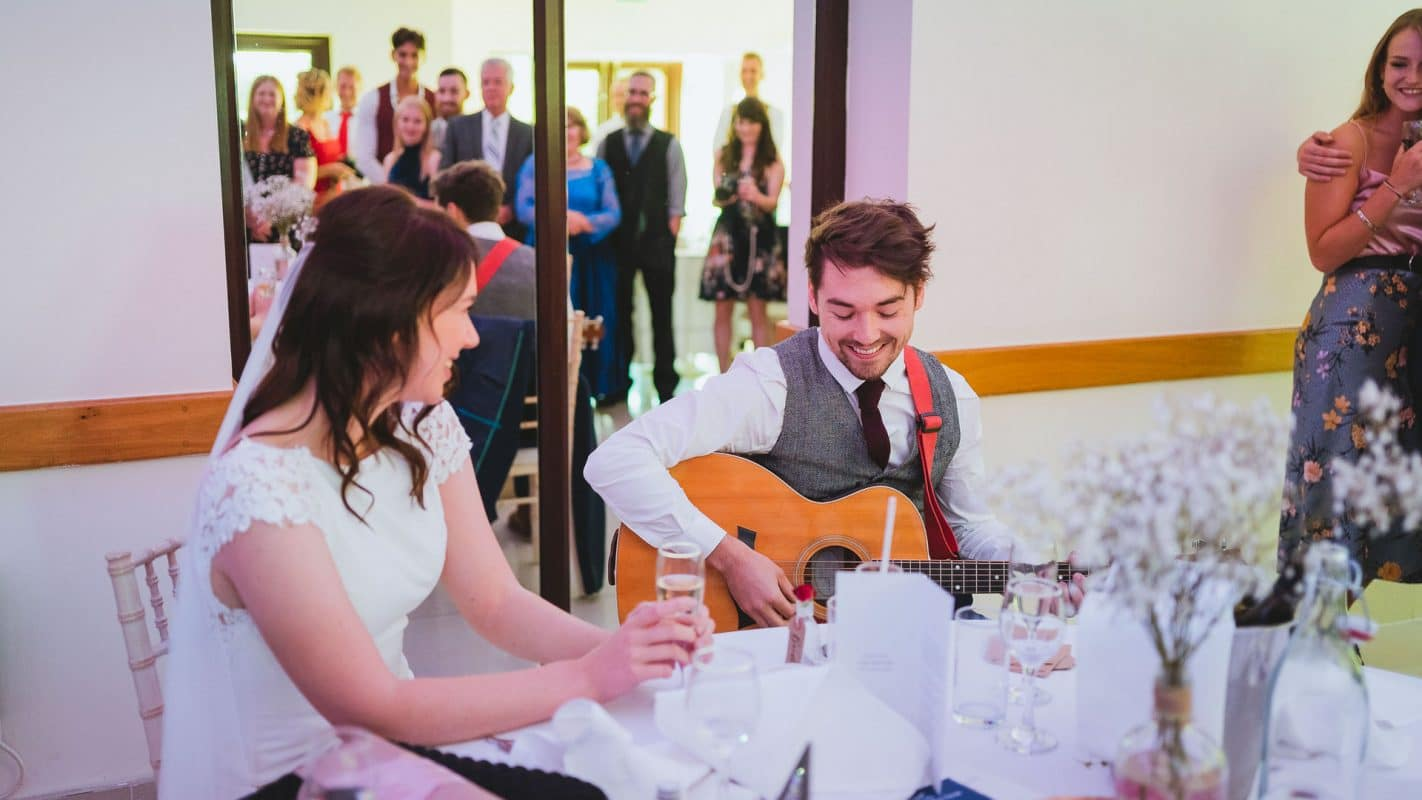 groom singing with guitar to bride