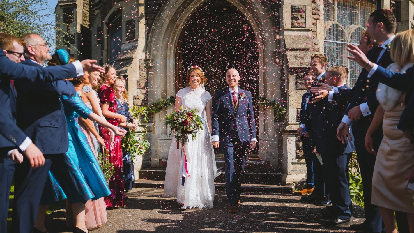 Bride and groom exiting to confetti throwing guests
