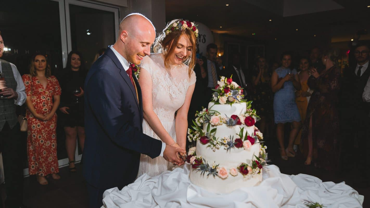 cutting of the cake by bride and groom at Holm House