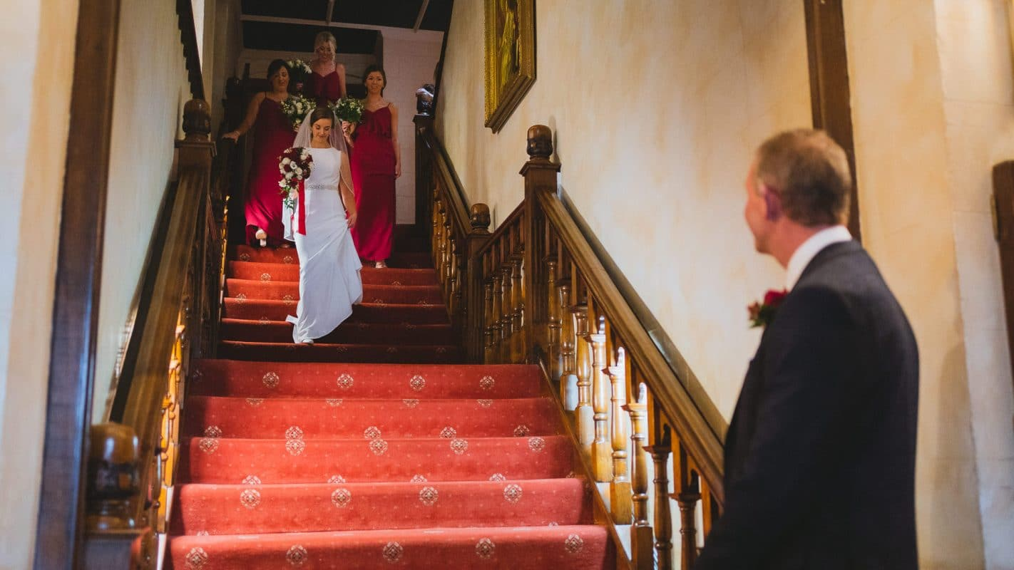 bride walking down stairs ahead of her wedding ceremony