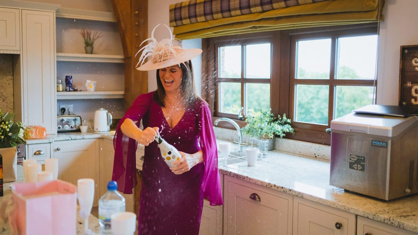 mother of the bride opening champagne at Mulberry house