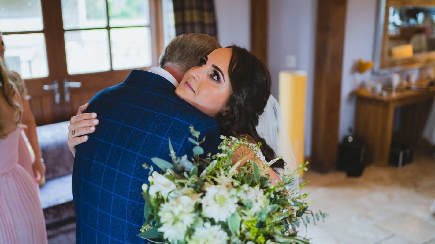 bride shedding a tear hugging her father