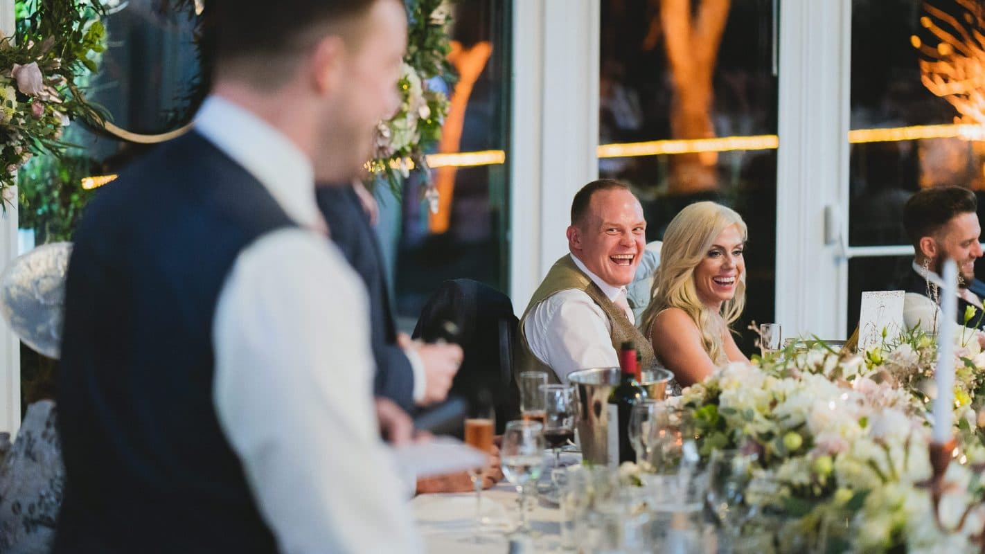 bride and groom laughing to groomsmen speeches