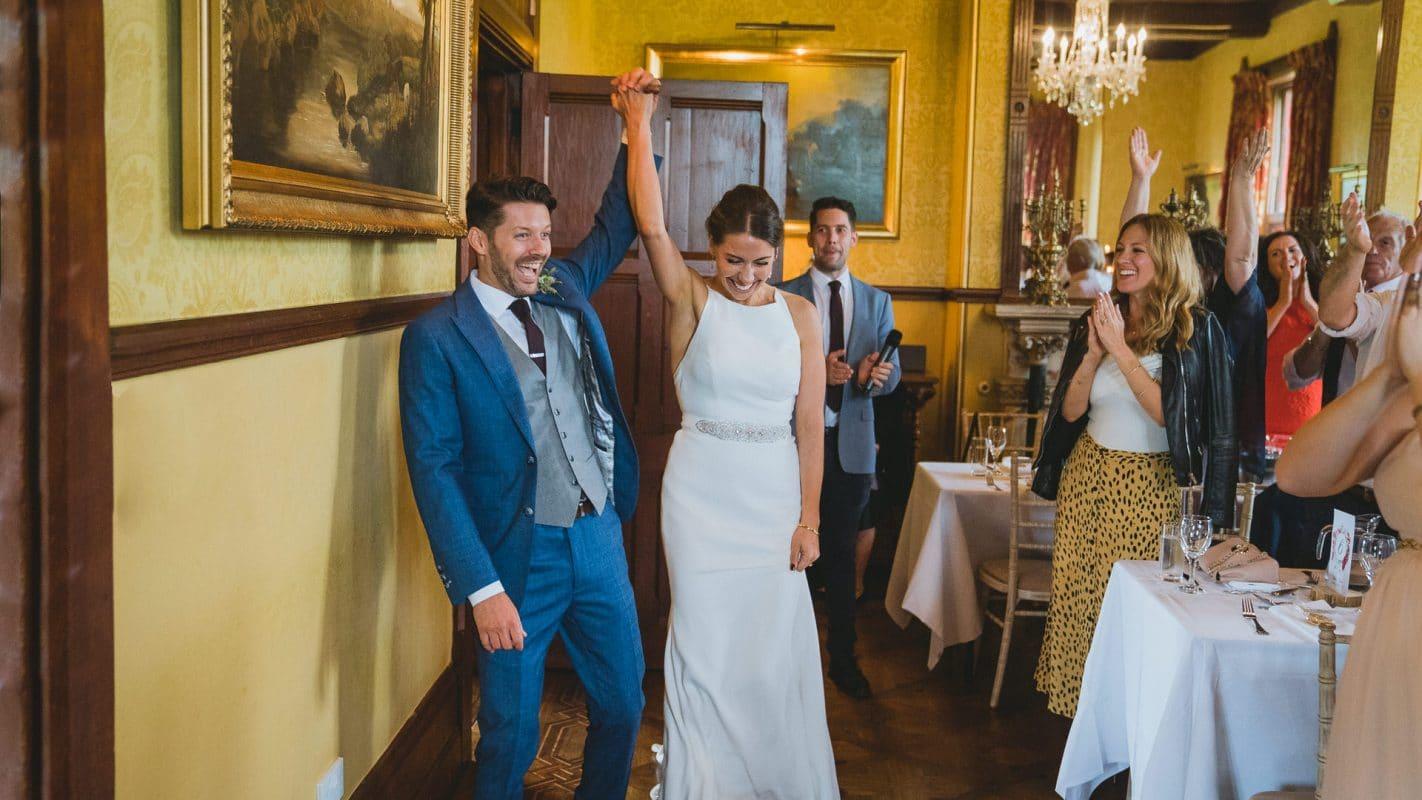 Bride and groom walk in on their wedding reception
