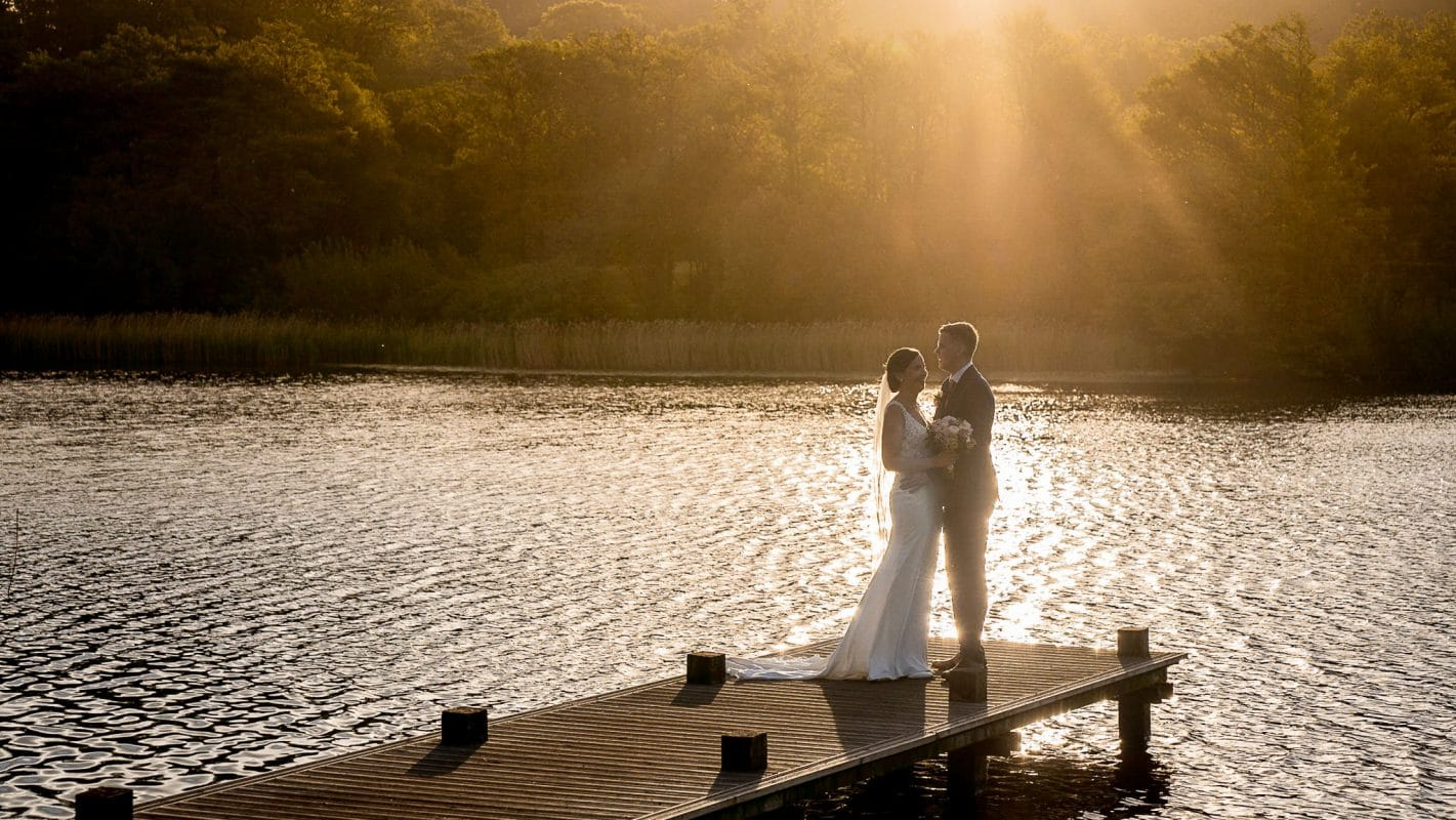 Bride and groom at the end of the jetty at sunset at Hensol Castle