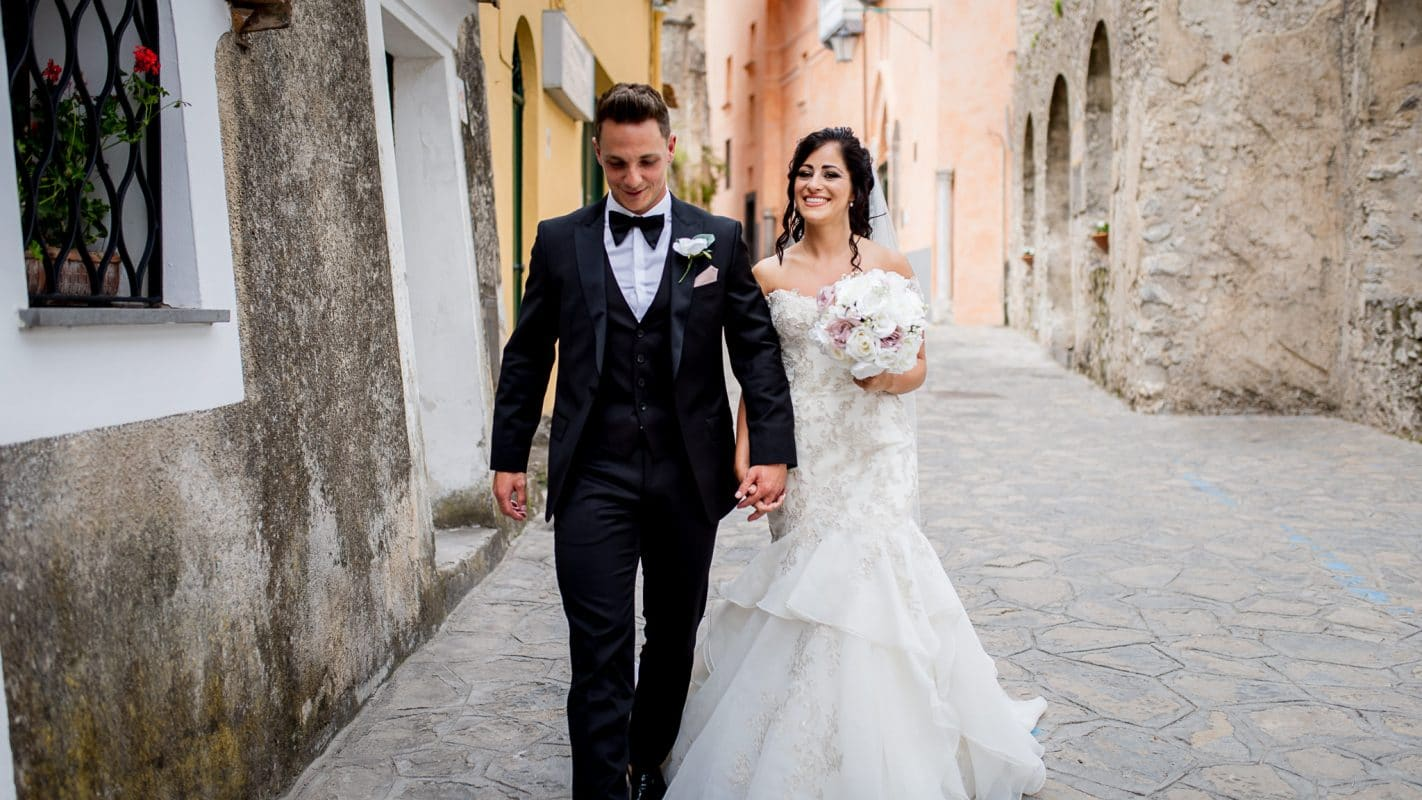 bride and groom walking through streets of Ravello, Italy on their wedding day