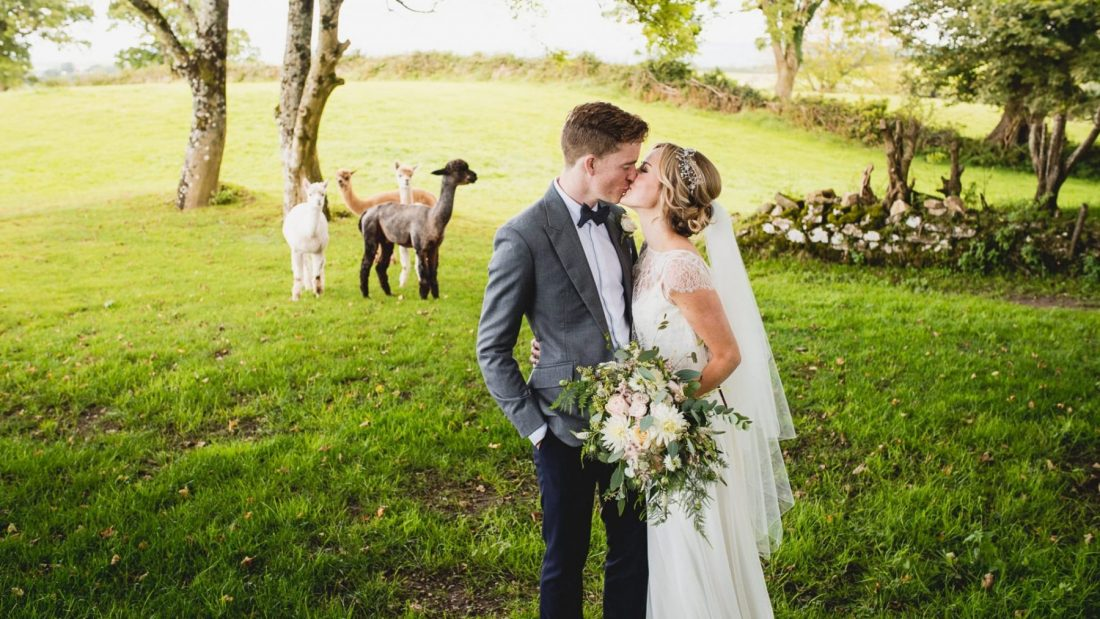 Cardiff wedding photographer capturing bride and groom kissing outside church